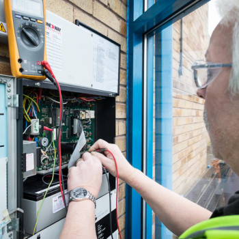 clseup of electrician testing fusebox of fire alarm system