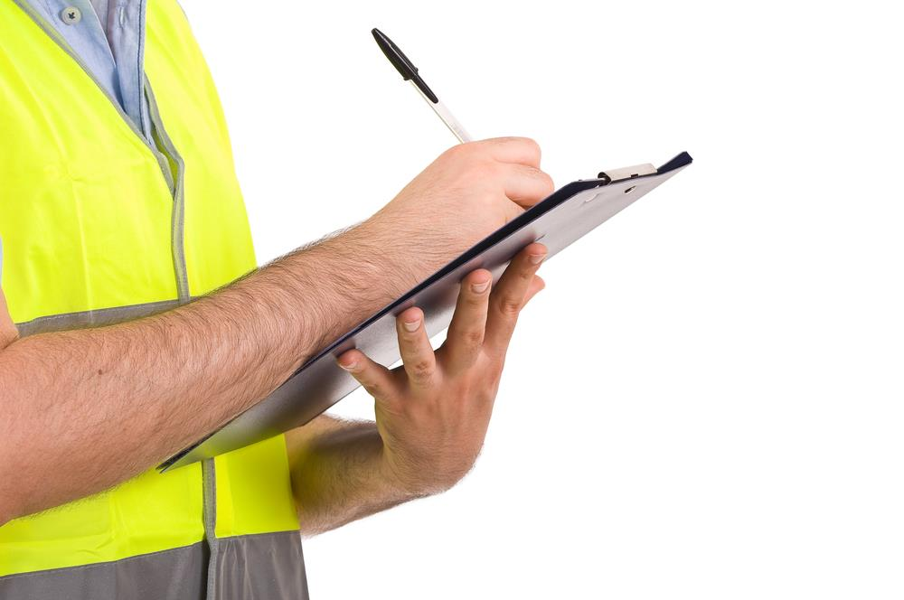 man in yellow vest holding clip board